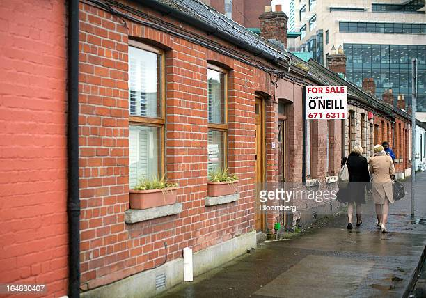 Pedestrians walk past an estate agent's board advertising a property 'For Sale' on a row of terraced houses in Dublin Ireland on Friday March 15 2013...