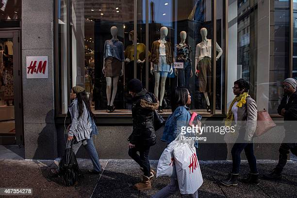 Pedestrians walk past an Hennes Mauritz AB store in the Center City area of Philadelphia Pennsylvania US on Saturday March 21 2015 The Bloomberg...