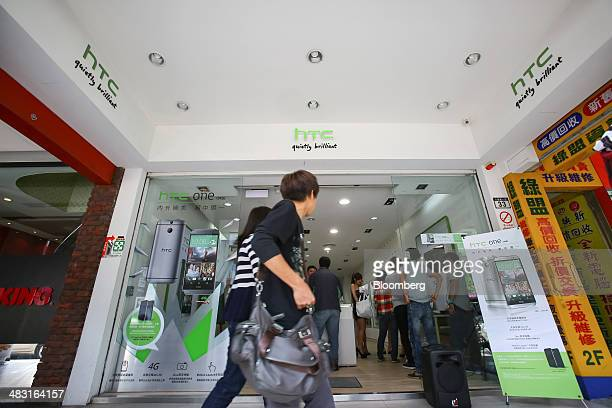 Pedestrians walk past an HTC Corp store displaying advertisements for the HTC One M8 smartphone in Taipei Taiwan on Saturday April 5 2014 HTC last...