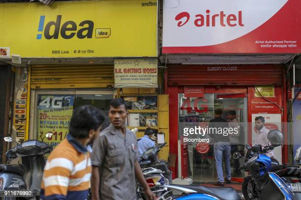Pedestrians walk past an Idea Cellular Ltd and a Bharti Airtel stores in Mumbai India on Saturday Jan 27 2018India's economy is expected to grow at...