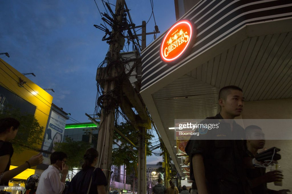 Pedestrians walk past an illuminated sign for a Chester's Grill restaurant in Bangkok, Thailand, on Friday, Aug. 11, 2017. Thai Beverage, the spirits giant that makes Chang beer and SangSom rum, is expanding into the fast-food business to take advantage of the rising appetite for fried chicken in Asia. ThaiBev agreed to purchase more than 240 existing KFC restaurants in Thailand for about 11.3 billion Thai baht ($340 million). Photographer: Brent Lewin/Bloomberg via Getty ImagesLewin/Bloomberg via Getty Images
