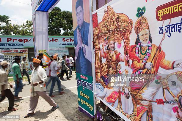 Pedestrians walk past an illustration of Indian Prime Minister Narendra Modi right as Lord Krishna sitting on a horse in Muzaffarpur Bihar India on...