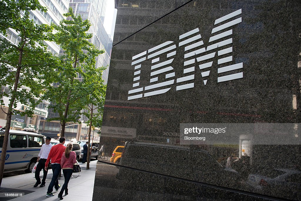Pedestrians walk past an International Business Machines Corp. (IBM) logo that is displayed in front of the company's offices in New York, U.S., on Monday, Oct. 14, 2013. International Business Machines is scheduled to report 3Q results post-market tomorrow. Photographer: Craig Warga/Bloomberg via Getty Images
