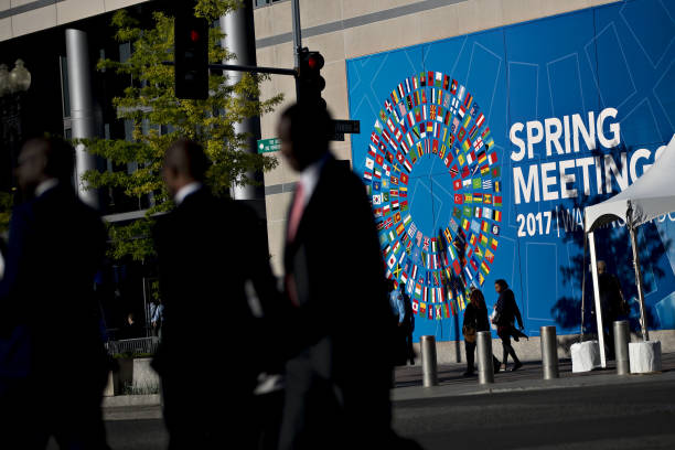World economic outlook is released during imf world bank spring pedestrians walk past an international monetary fund imf and world bank spring meeting sign sciox Images