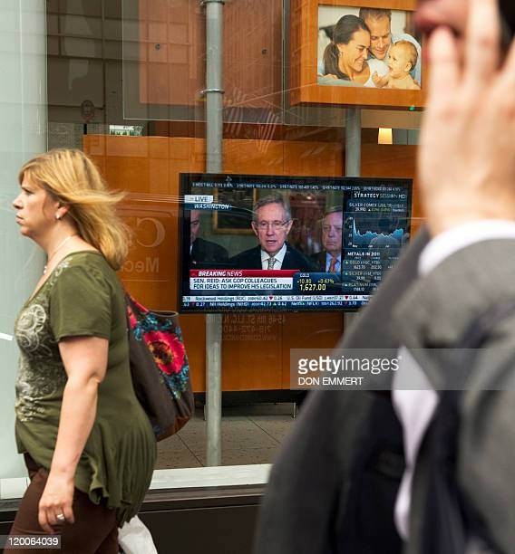 Pedestrians walk past an office with a tv monitor in the window broadcasting a news conference with Senator Majority Leader Harry Reid July 29 2011...
