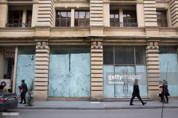 Pedestrians walk past an unoccupied retail space in Baku Azerbaijan on Friday March 16 2018 Azerbaijan's economy barely returned to growth last year...