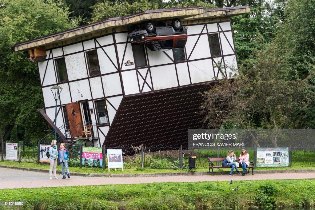 Pedestrians walk past an upside down house in a park in ...