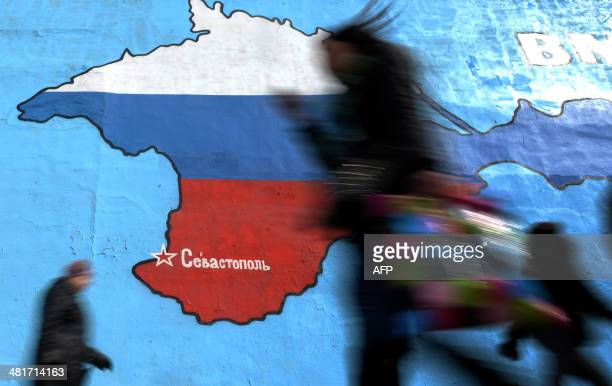 Pedestrians walk past an wall painting depicting a map of Crimean peninsula bearing the colours of Russia's national flag in Moscow on March 31 2014...