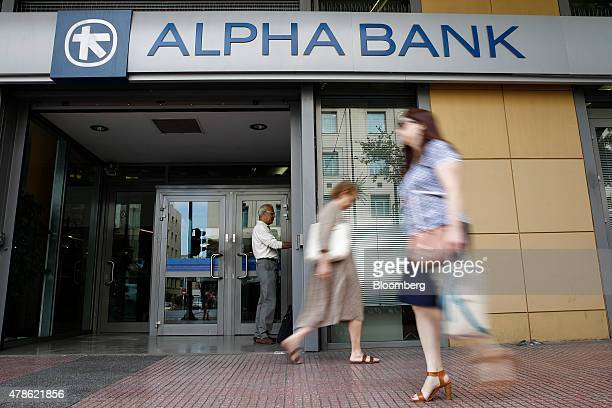 Pedestrians walk past as a customer uses an automated teller machine at an Alpha Bank AE bank branch in Athens Greece on Friday June 26 2015 Greek...