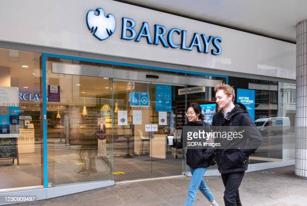 Pedestrians walk past Barclays bank, a British multinational investment bank and financial services company, in London.