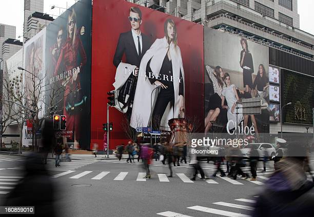 Pedestrians walk past billboards for Burberry Group Plc, left, and Cie. Financiere Richemont SA's Chloe brand outside a shopping mall under...