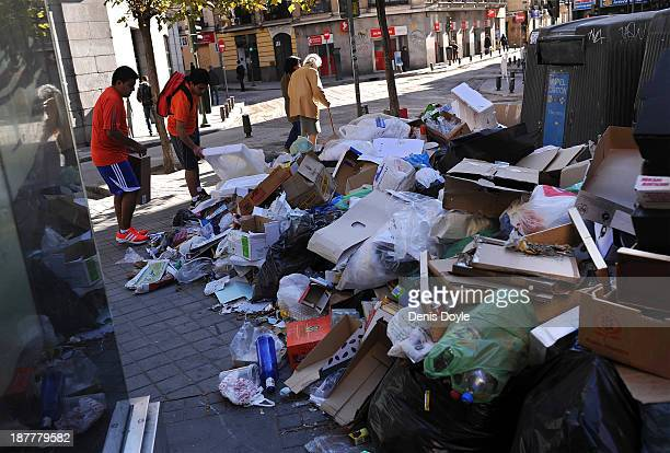 Pedestrians walk past bins overflowing with rubbish in the city centre on November 12 2013 in Madrid Spain Street cleaners garbage collectors and...