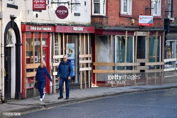 Pedestrians walk past boardedup shops ahead of the annual Royal Shrovetide Football Match in Ashbourne northern England on February 25 2020 The...