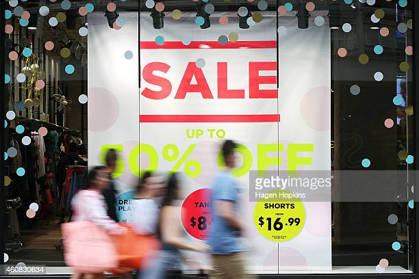 Pedestrians walk past Boxing Day sale signage on December 26 2014 in Wellington New Zealand Boxing Day is one of the busiest days for retail outlets...