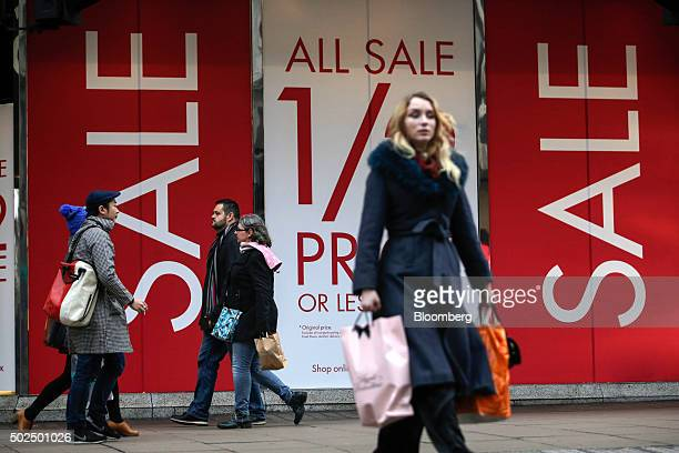 Pedestrians walk past Boxing Day sale signs on display at a BHS Ltd store on Oxford Street in London UK on Saturday Dec 26 2015 UK retail sales...