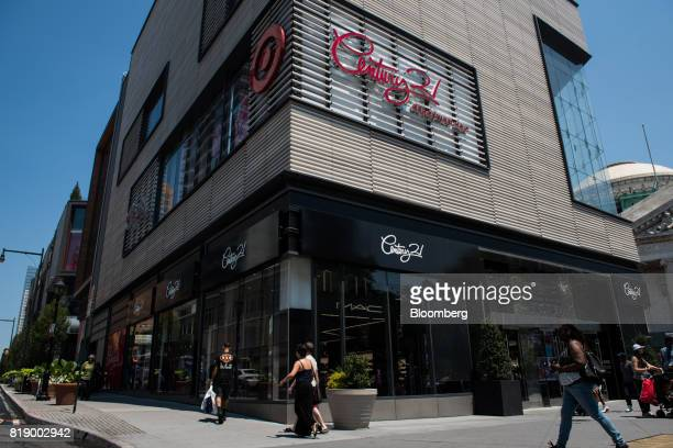 Pedestrians walk past Century 21 department store signage displayed outside of City Point in the Brooklyn borough of New York US on Wednesday July 19...