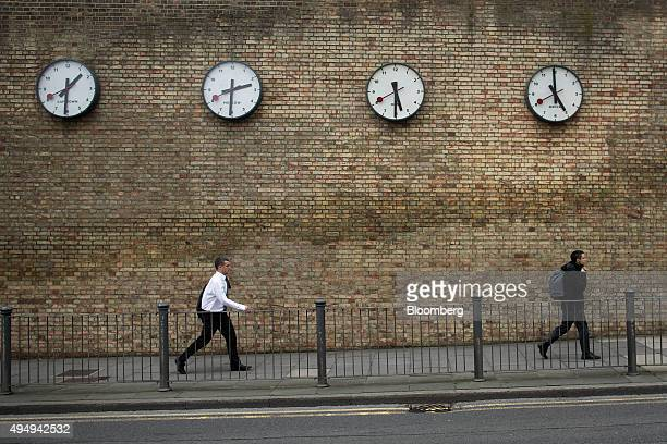 Pedestrians walk past clocks displaying world times in the Canary Wharf business financial and shopping district of London UK on Thursday Oct 29 2015...