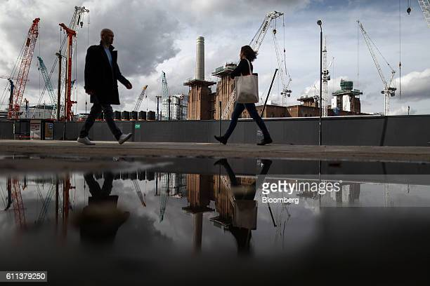 Pedestrians walk past construction cranes at the Battersea Power Station office retail and residential development which is backed by Sime Darby Bhd...