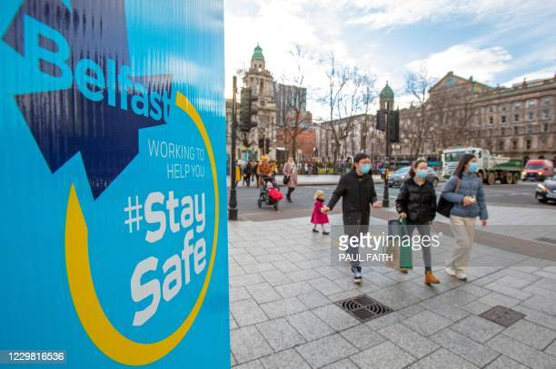 Pedestrians walk past COVID-19 informatin signs in Belfast on November 27 as stricter restrictions come in to force to help stem the spread of the...