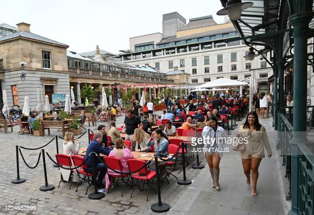 Pedestrians walk past customers sitting at outdoor tables in Covent Garden in London on July 4 as restrictions are further eased during the novel...