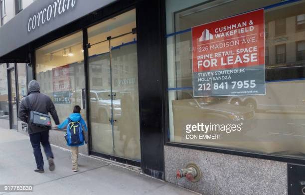 Pedestrians walk past empty retail space on Madison Avenue on February 8 2018 in New York The New York borough of Manhattan is richer and more...