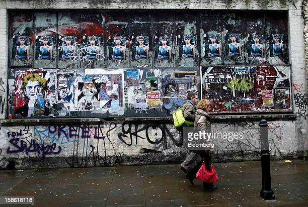 Pedestrians walk past fly posters and graffiti on a wall in London UK on Thursday Dec 20 2012 Britain's economy expanded less than previously...