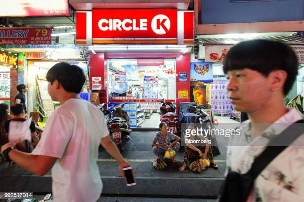 Pedestrians walk past food vendors sitting outside a Circle K store at night in Ho Chi Minh City Vietnam on Wednesday June 20 2018 For decades...