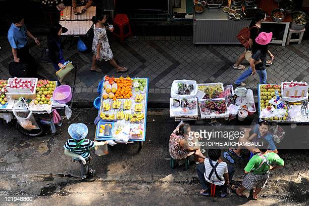 Pedestrians walk past fruit stalls along a street in downtown Bangkok on August 24 2011 Thailand's central bank on August 24 raised its key interest...