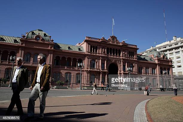 Pedestrians walk past Government House which houses the offices of President Cristina Fernandez de Kirchner in Buenos Aires Argentina on Wednesday...