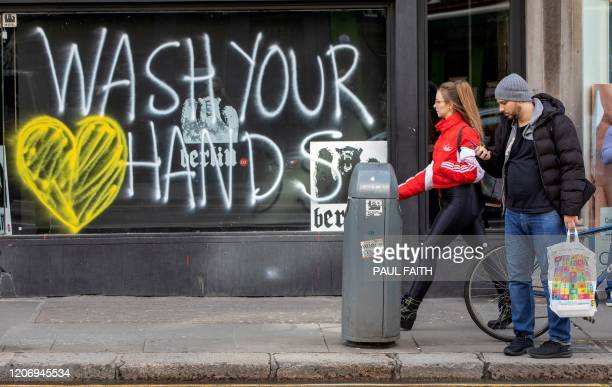 Pedestrians walk past graffiti urging people to 'wash their hands' in the Grafton Street area of Dublin City centre on March 13 as schools and...