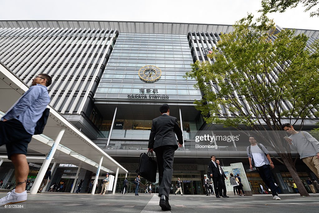 Pedestrians walk past Hakata Station in Fukuoka, Fukuoka Prefecture, Japan, on Tuesday, Oct. 11, 2016. Kyushu Railway Co., the state-owned bullet-train operator seeking to raise as much as 416 billion yen ($4 billion) in an initial public offering, plans to reduce its reliance on Japan by investing in residential and office properties in Southeast Asia, its chairman said in an interview. Photographer: Akio Kon/Bloomberg via Getty Images