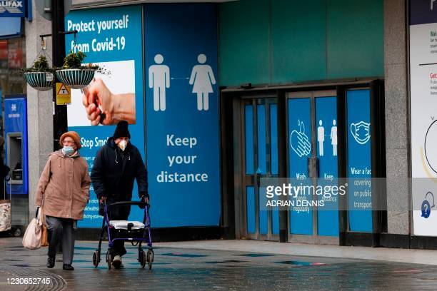 Pedestrians walk past hoarding with advice on how to stay safe during the Covid-19 pandemic on the high street in Slough, west of London, on January...