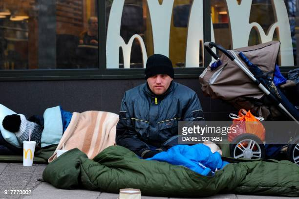 Pedestrians walk past homeless man James in his spot on High Street opposite Windsor Castle in Windsor west of London on February 2 2018 In...