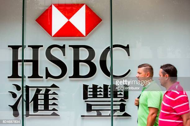 Pedestrians walk past HSBC signage in the Admiralty district of Hong Kong on July 31 2017 HSBC said on July 31 pretax profit for the first half of...