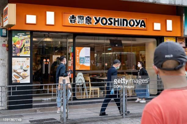 Pedestrians walk past Japanese fast-food chain Yoshinoya restaurant seen in Hong Kong.