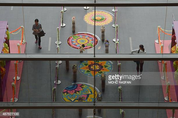 Pedestrians walk past 'kolams' made of coloured rice grains at a shopping mall ahead of the Diwali or Deepavali festival in Kuala Lumpur on October...