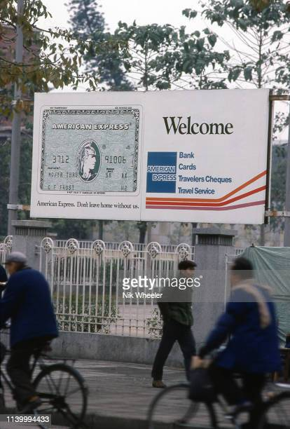 Pedestrians walk past large billboard advertisement for American Express Credit Cards on street in Guangzhou, formerly Canton, circa 1980:
