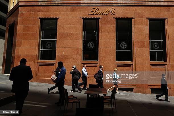 Pedestrians walk past Lindt Spruengli AG's chocolate cafe at Martin Place in Sydney Australia on Tuesday Oct 23 2012 Treasurer Wayne Swan on Monday...