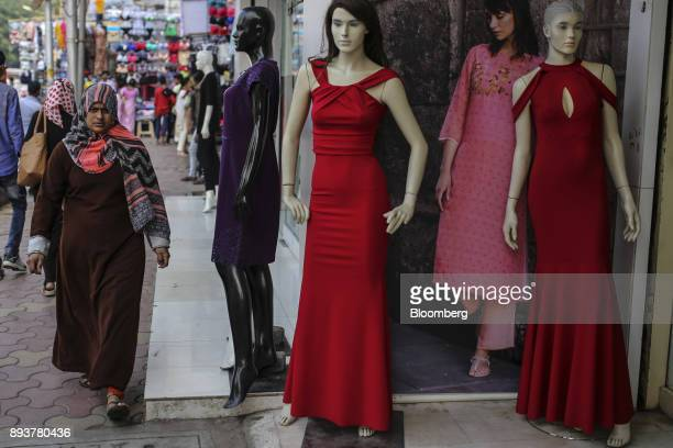 Pedestrians walk past mannequins displayed outside a clothing store in Mumbai India on Friday Dec 15 2017 India's inflation surged past the central...