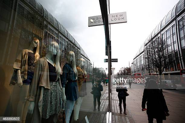 Pedestrians walk past mannequins displaying clothes in the window of a New Look fashion store operated by New Look Group Ltd on Oxford Street in...
