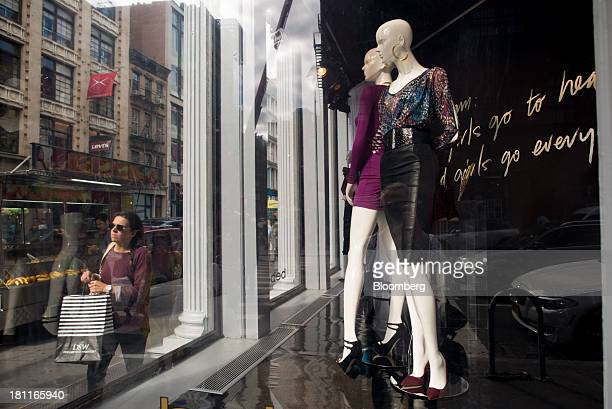 Pedestrians walk past mannequins in the window of a Bebe Stores Inc shop in the shopping district of Soho in New York US on Saturday Sept 14 2013...