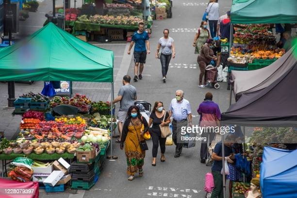 Pedestrians walk past market stalls selling fresh fruit and vegetables in Croydon, Greater London, U.K., on Monday, Aug. 17, 2020. The relief as...