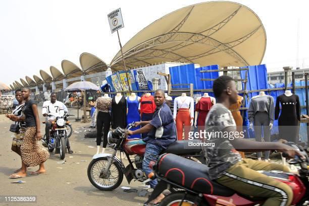 Pedestrians walk past motorists standing near street stalls in Lagos Nigeria on Saturday Feb 16 2019 A lastminute delay of Nigerias general elections...