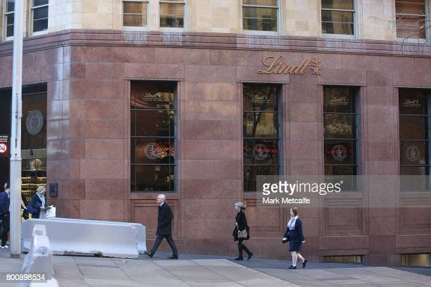 Pedestrians walk past newly installed anti terror bollards outside Lindt cafe in Martin Place on June 26 2017 in Sydney Australia The large concrete...