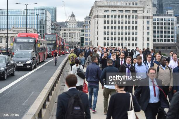 Pedestrians walk past newly installed barriers on London Bridge in London on June 8 2017 following the June 3 terror attack that targeted members of...