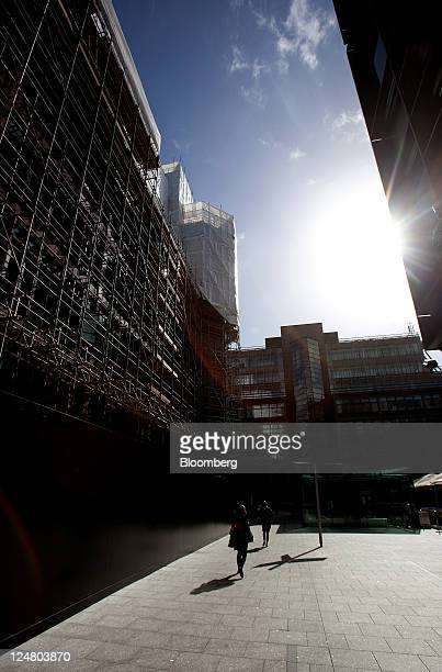 Pedestrians walk past number 4 Broadgate as construction work is underway on the new London headquarters for UBS AG at the site owned by British Land...