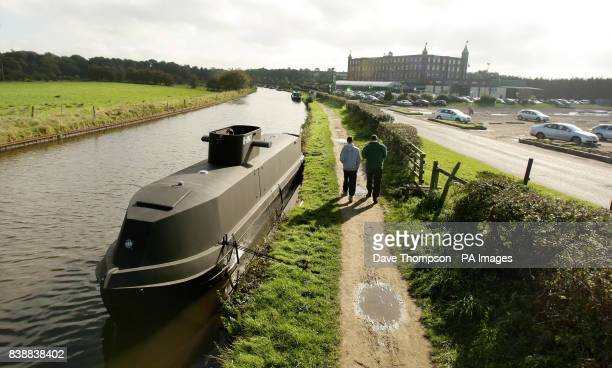 Pedestrians walk past of a canal barge transformed into a replica of a German UBoat on the LeedsLiverpool canal in Botonay Bar near Chorley Lancashire