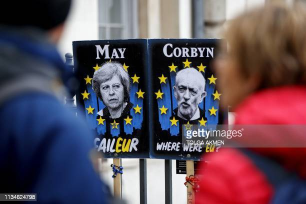 Pedestrians walk past placards featuring Britain's Prime Minister Theresa May and opposition Labour party leader Jeremy Corbyn near the Houses of...