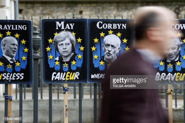 TOPSHOT Pedestrians walk past placards featuring Britain's Prime Minister Theresa May and opposition Labour party leader Jeremy Corbyn near the...
