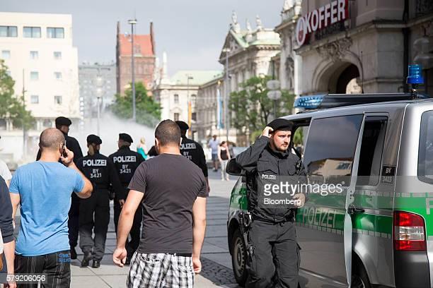 Pedestrians walk past police officers as they patrol in Karlsplatz in Munich Germany on Saturday July 23 2016 German Chancellor Angela Merkel will...